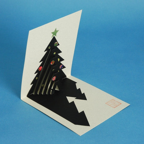 Kyoko Niikuni has created this pop-out card of a Christmas tree as a variation of her practice of kiri-e, a traditional Japanese cut paper art.