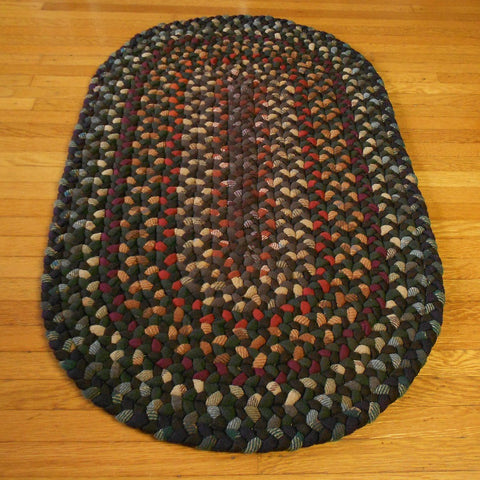 This thick hand braided oval rug features deep autumn leaf shades of brown, olive, rust, red, orange, and maroon.