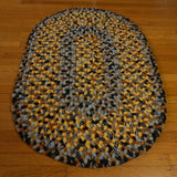 This oval hand braided wool rug features an interesting blend of gold, gray, black, and brown.