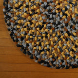 Detail of oval hand braided wool rug featuring an interesting blend of gold, gray, black, and brown.