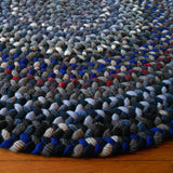 Detail of round hand braided rug that has several shades of blue and accents of white, black, and deep red.