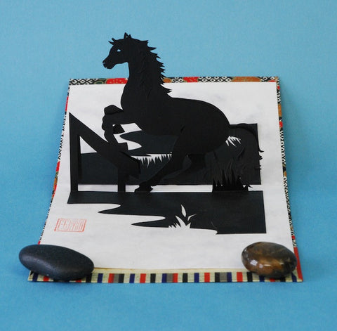 This 3-dimensional papercut sculpture of a jumping horse is an example of kiri-e, a traditional Japanese cut paper art.