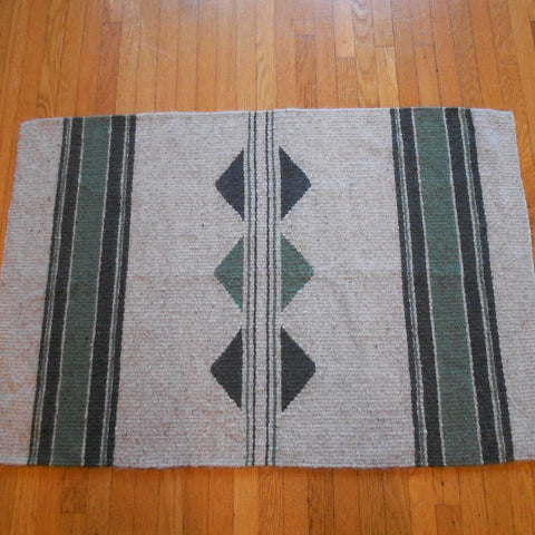 This is a handwoven Navajo-Churro wool rug with stripes and a split diamond shape by Linda Morton-Keithley of Idaho.