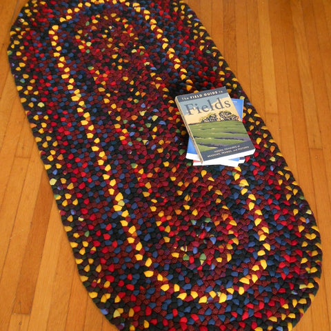 This multicolored braided wool runner features a mixture of bright colors including red, black, blue, yellow, and purple.