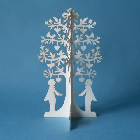 A papercut tree of a groom and groom can sit atop a wedding cake or be used in other ways to celebrate the marriage of two men.