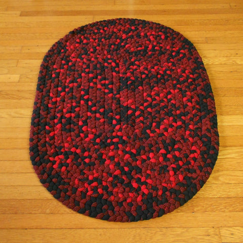 This classic black and red oval wool rug was hand braided in Oregon. It measures 22 in x 33 in.