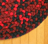 Detail of hand braided wool rug in red and black