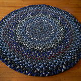 This round hand braided wool rug has several shades of blue and accents of white, black, and deep red.