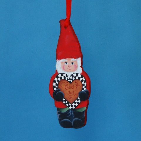 "A rosemaling artist from Colorado painted this wooden Christmas ornament with a wooden tomte figure carrying a heart bearing the words ""God Jul"" (Merry Christmas)."
