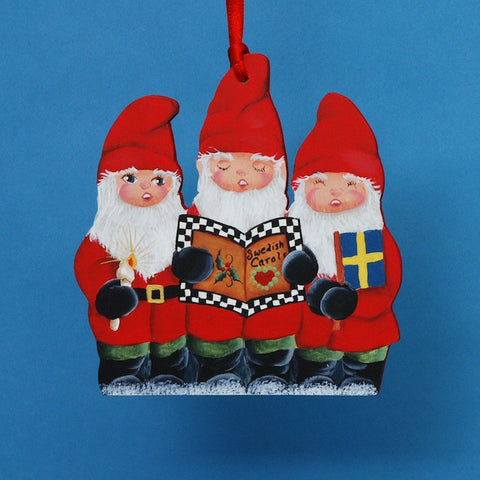 The artist from Colorado used Scandinavian rosemaling techniques to paint three caroling tomte figures onto a wooden Christmas ornament.