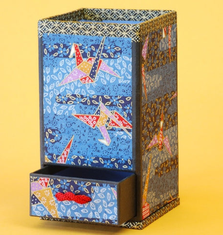 This washi kogei box created by Kyoko Niikuni features washi paper printed with red and gold origami cranes on a blue background.