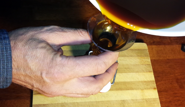 funneling spicy chai syrup into a swing-top bottle