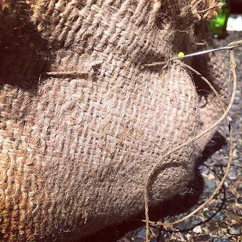 continuing to sew burlap with twine