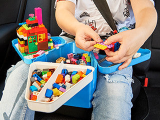 Child playing with blue Teebee portable toy box in car