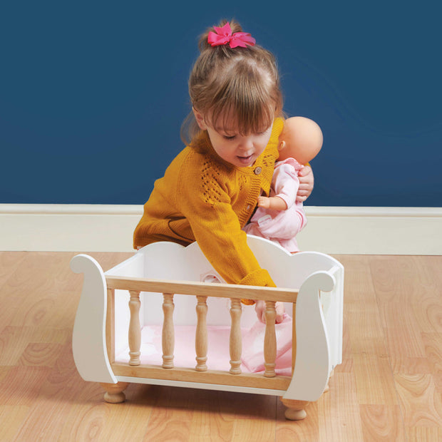 Girl playing with White wooden Sleigh Doll Cot with pink bedding