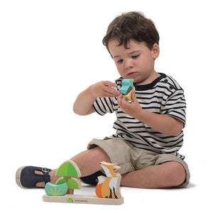 Young boy playing with wooden fox stacker toy by Tenderleaf