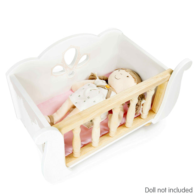 Doll sleeping in white wooden Sleigh Doll Cot with pink bedding