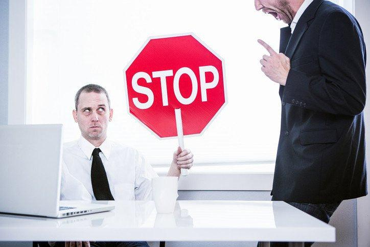 Employee holding a sign that says stop; Managing 'brilliant jerks' | Leadership IQ