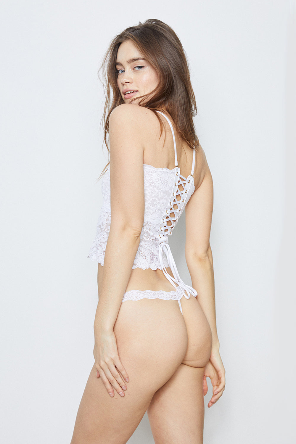 White lace-up reversible cropped lingerie cami made of stretch lace.