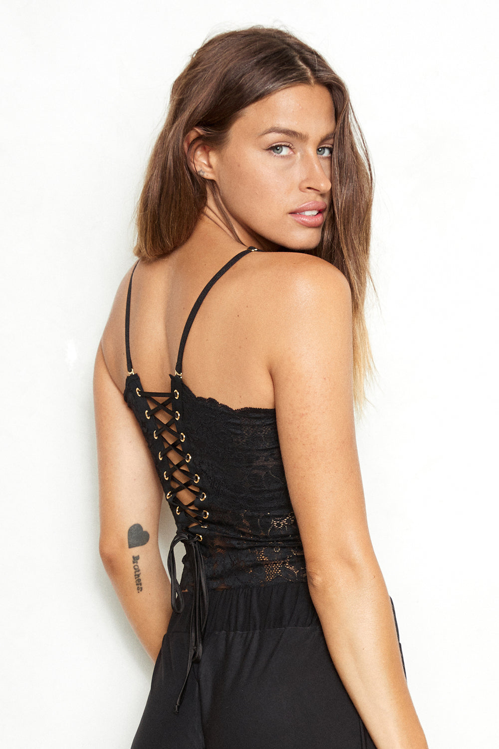 Black lace-up reversible cropped lingerie cami made of stretch lace.