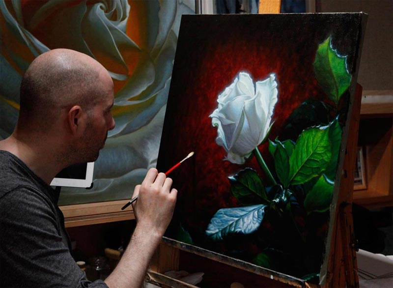 Vincent Keeling painting a white rose, with red background