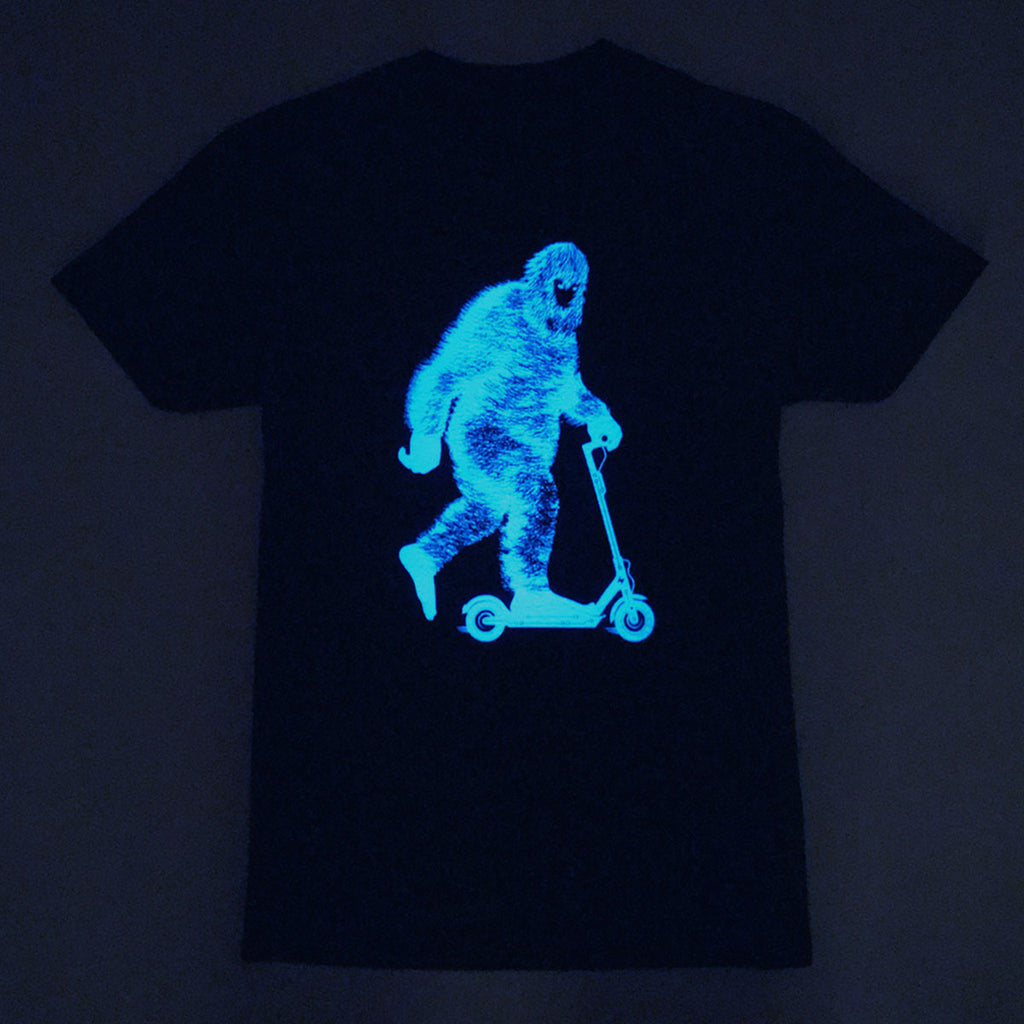 Glowing Bigfoot on an Electric Scooter Graphic Tee by STORY SPARK