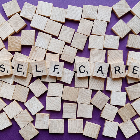 Self care spelled in Scrabble pieces