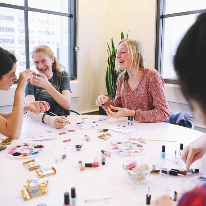 Girls around a table laughing and making nail polish