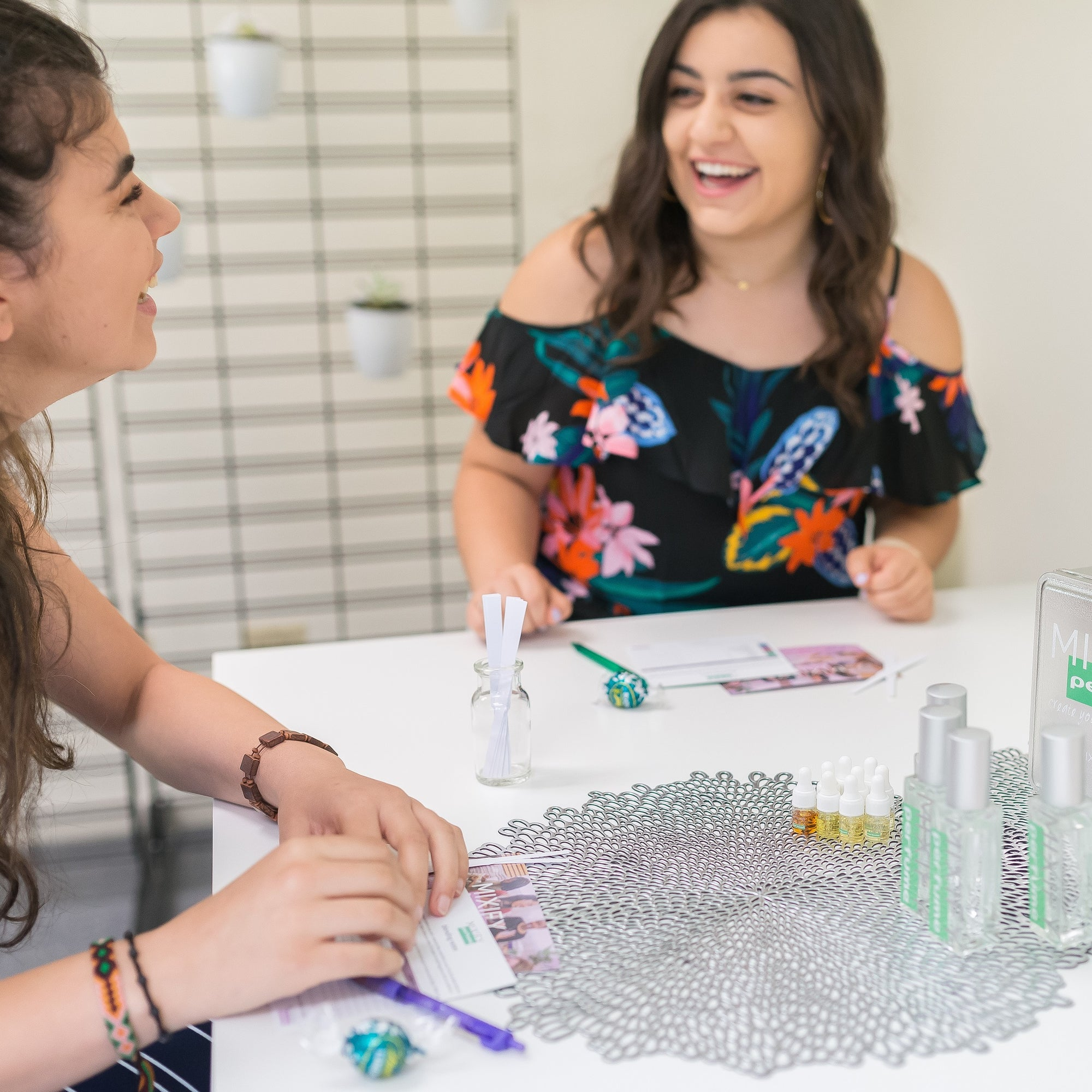 Girls laughing around table making Mixify Beauty perfume