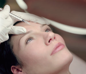 woman receiving anti-wrinkle injection treatment to forehead