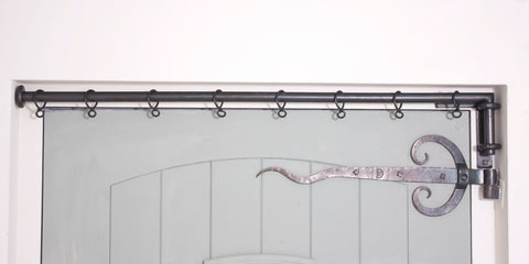 Wrought iron drapery arm fitted in door recess with L-shaped bracket