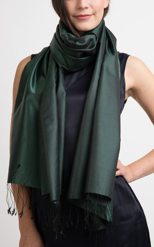 model wearing a reversible silk wrap pashmina shawl in plain forest green and dark green, made out of pure silk from The Little Tibet