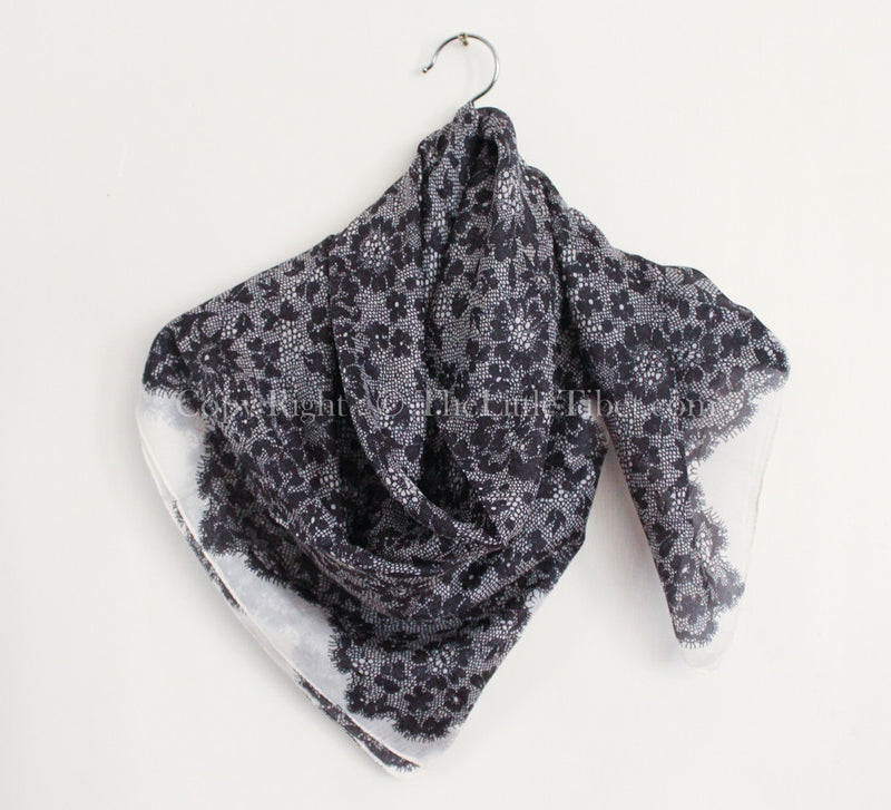 100% pure silk luxury monochrome lace scarf with floral detail draped around shoulders