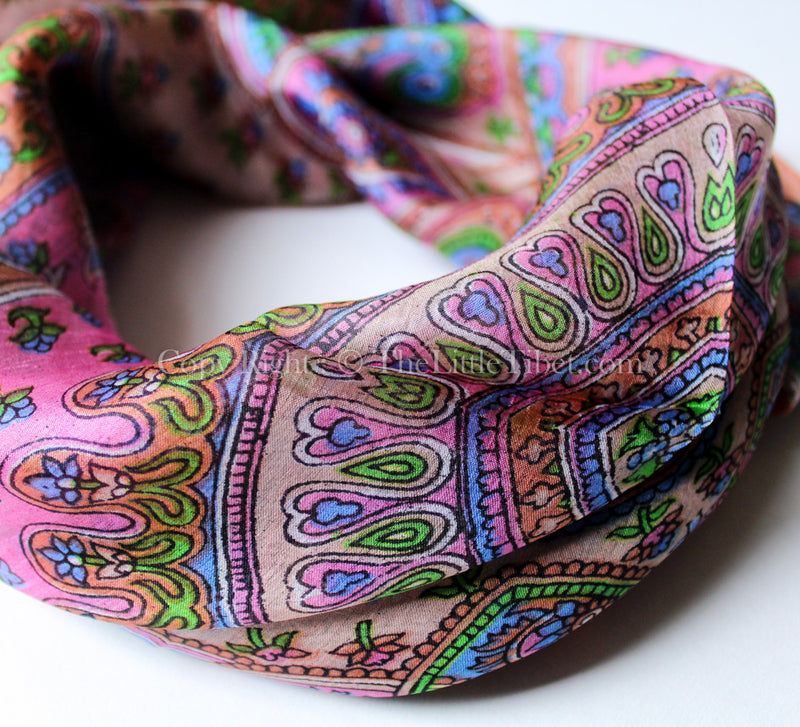 close up of Square shaped 100% silk scarf with candy pink, blue and green paisley pattern