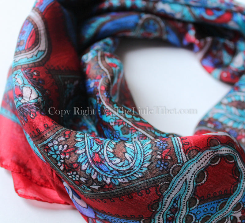 Close up of Crimson red and turquoise paisley patterned square shaped 100% silk scarf