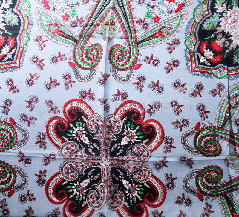 Close up of 100% silk scarf Symmetrical patterned  with black, green and red printed accents