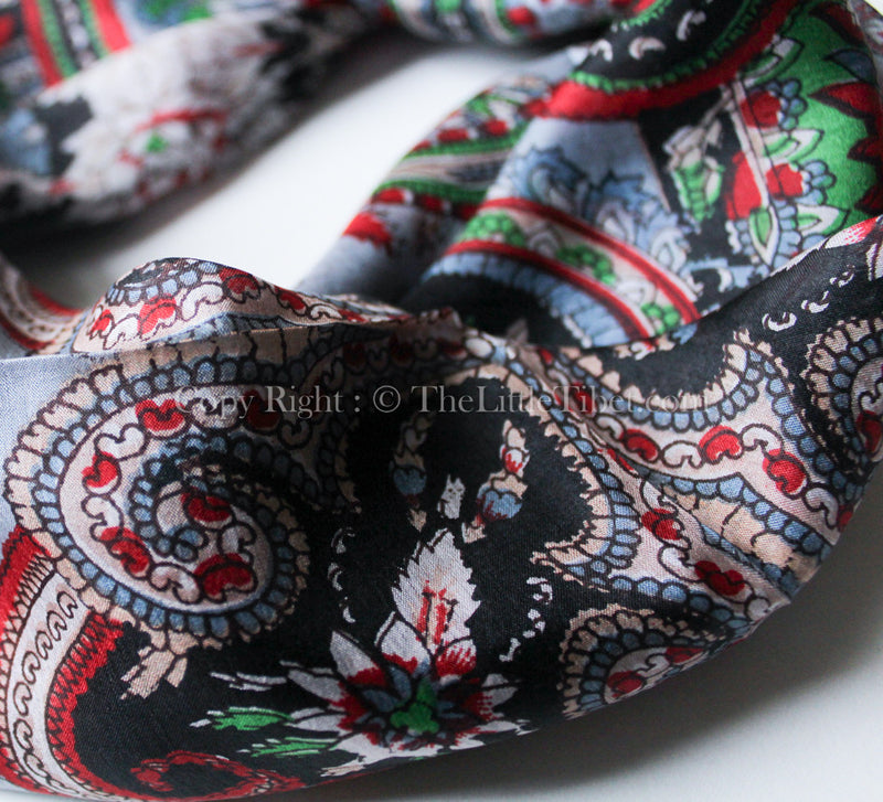 close up of symmetrical pattern 100% silk scarf with green, black and red detail