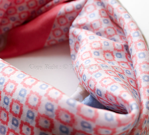 Close up of 100% square silk scarf with baby blue, light coral and brown detail