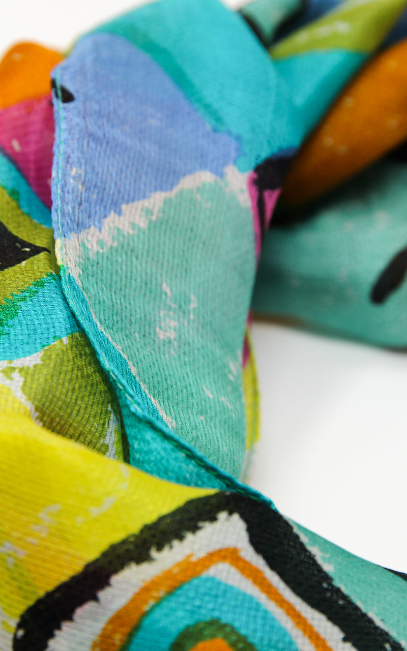 close up of Geometrical designed summer lightweight silk scarf with vibrant blue colours