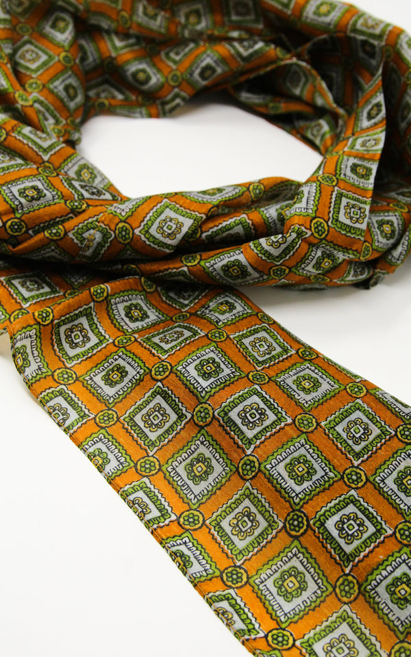 close up of soft touch  dark orange and green patterned pure silk scarf
