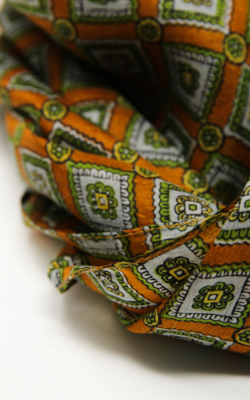 close up of dark orange and green patterned 100%  silk scarf