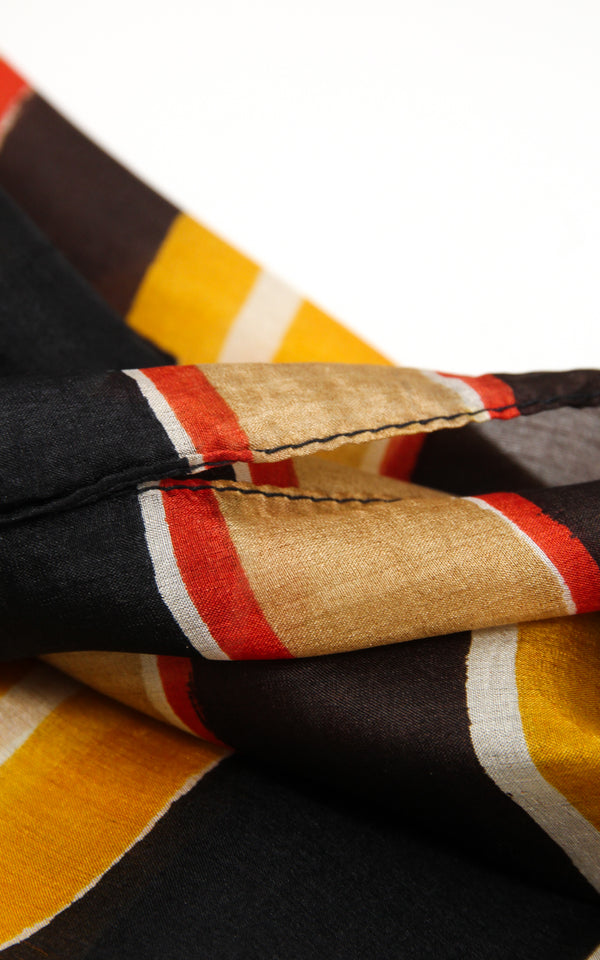 Close up of stripey patterned silk scarf with yellow beige and black  accents