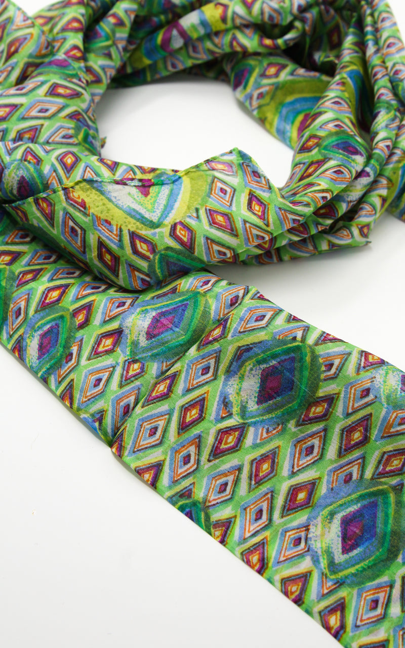 Close up of vibrant green peacock green patterned elegant 100% silk scarf