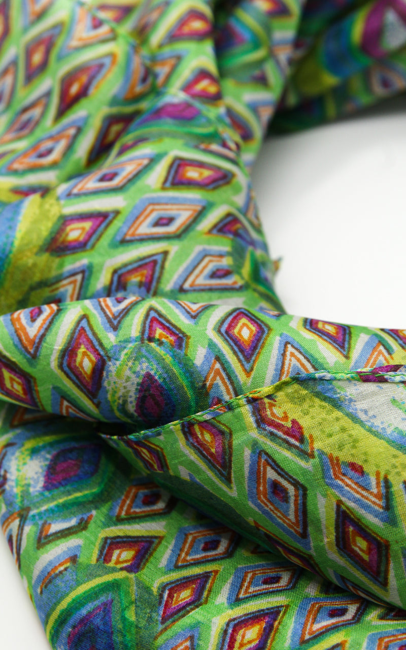 Close up of stylish bright green peacock green patterned  100% silk scarf