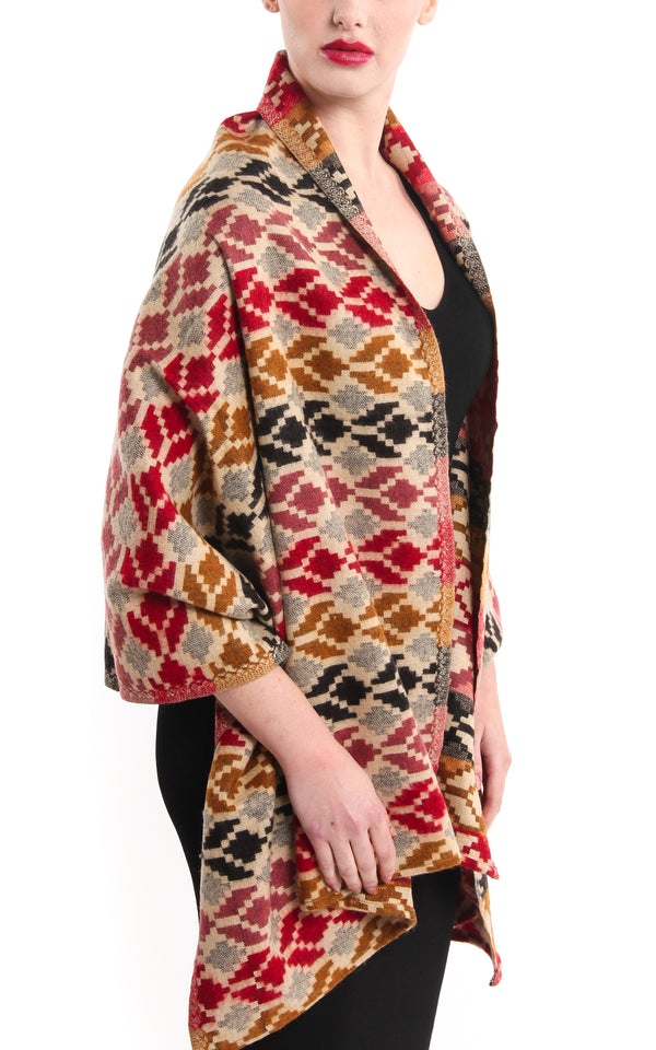 Geometric snowflake pattern tibet shawl with red beige back accents draped around shoulder