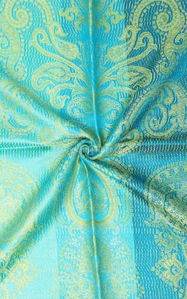 Close up of Vibrant green pure silk pashmina with bright blue accents and paisley detail