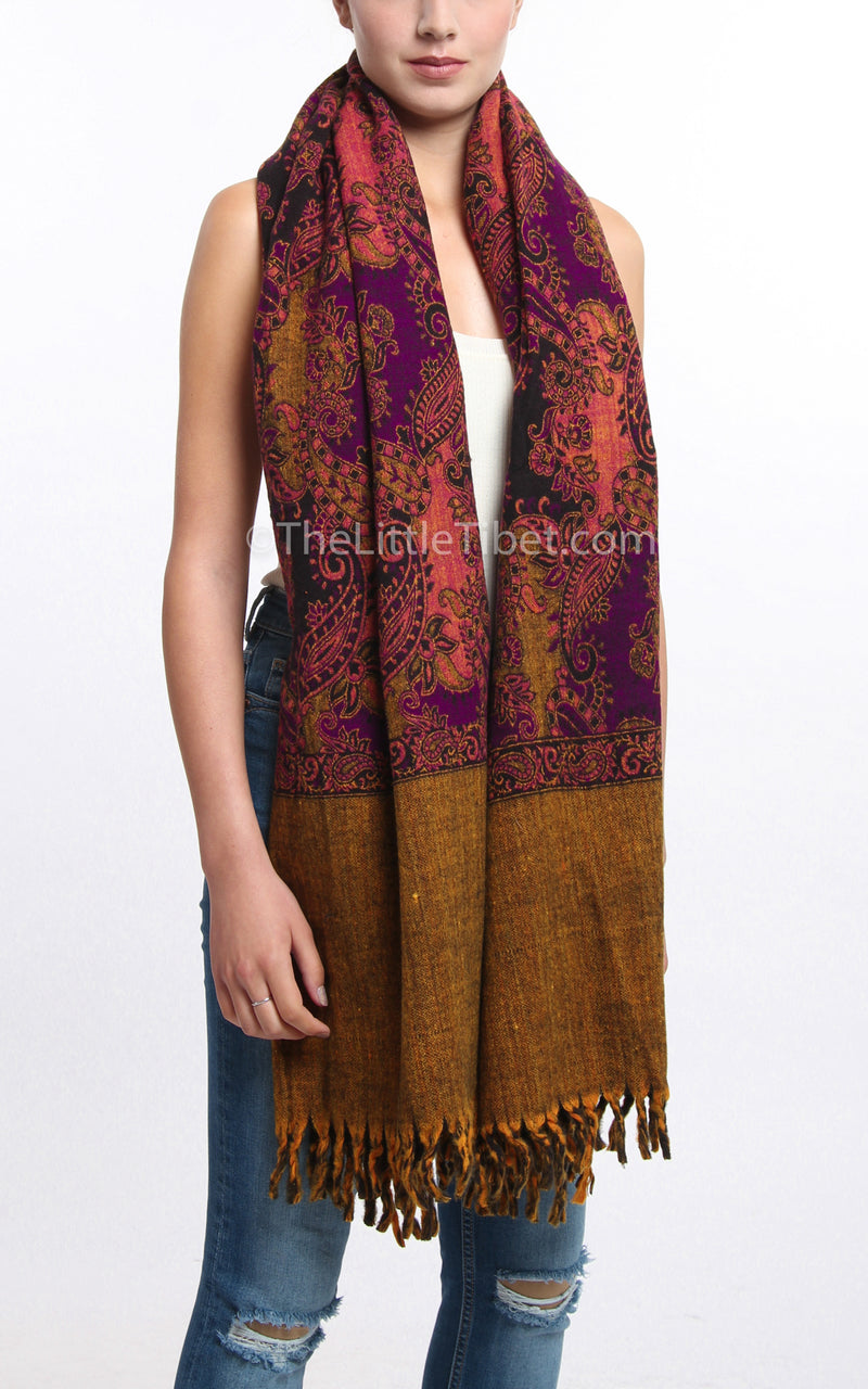 Multi-coloured pink paisley designed  tibet shawl with tassels draped around shoulders
