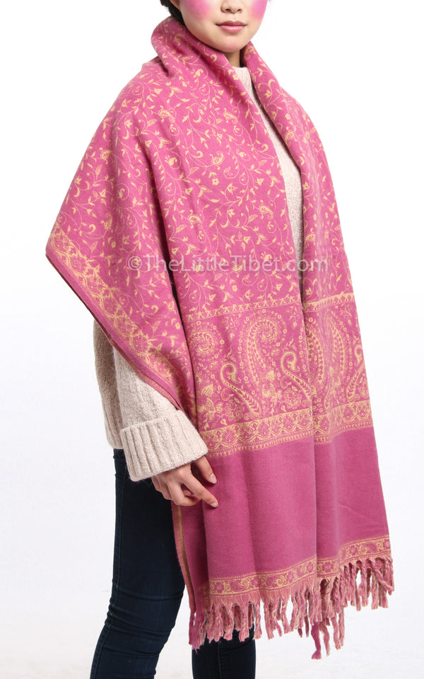 Bubblegum pink cream paisley design reversible tibet shawl  with tassels draped around shoulders