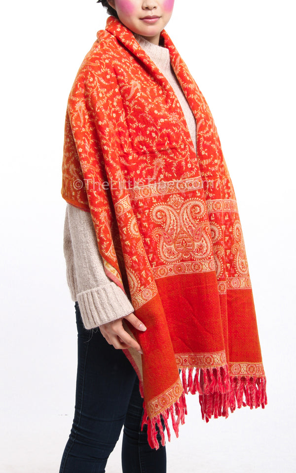 Autumnal orange cream paisley design reversible tibet shawl draped around the shoulders