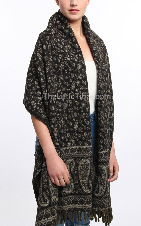 Dark green cream paisley design reversible tibet shawl  with tassels draped around shoulders